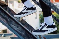 Chłopiec wspina się schodki z jego nowymi sneakers fotografia royalty free