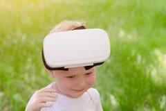 Chłopiec wziąć daleko jego rzeczywistość wirtualna hełm Zielona trawa na t zdjęcie stock