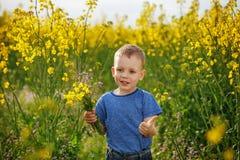 Chłopiec z bukietem kwiaty jest w żółtym kwieceniu Obrazy Royalty Free