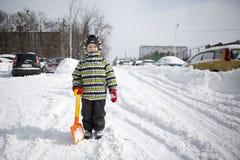 Chłopiec z dużą łopatą rozjaśniać śnieg Obrazy Stock