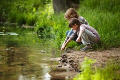 Chłopiec z dziewczyną blisko wody Obraz Royalty Free