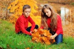 Chłopiec z dziewczyną chodzi w jesień parku Zdjęcia Stock