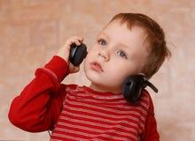 Chłopiec z hełmofonami w domu Obrazy Stock