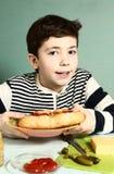 Chłopiec z jaźnią robić ogromnemu hotdog ono uśmiechać się Fotografia Royalty Free