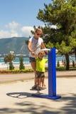 Chłopiec z jego matką na ulicznym robi sprawność fizyczna trenerze Obrazy Royalty Free