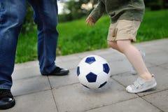 Chłopiec z jego ojcem ma zabawę bawić się mecz piłkarskiego na pogodnym letnim dniu Obraz Royalty Free