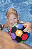Chłopiec z kolor piłką jest w pływackim basenie Fotografia Royalty Free