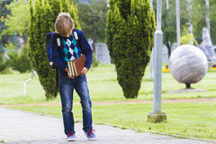 Chłopiec z książkami w jego rękach iść szkoła plenerowy Zdjęcie Stock