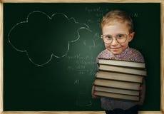 Chłopiec z książki pobliskim szkolnym chalkboard Obrazy Royalty Free
