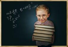 Chłopiec z książki pobliskim szkolnym chalkboard Obraz Royalty Free