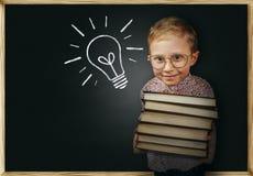 Chłopiec z książki pobliskim szkolnym chalkboard Zdjęcia Stock