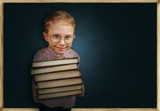 Chłopiec z książki pobliskim szkolnym chalkboard Zdjęcie Stock