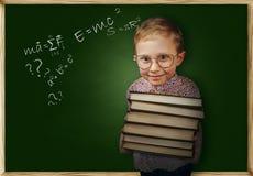 Chłopiec z książki pobliskim szkolnym chalkboard Zdjęcia Royalty Free
