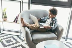 Chłopiec z laptopem w karle obraz royalty free