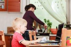 Chłopiec z laptopu i matki kucharstwem w kuchni obrazy stock