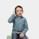 Chłopiec z mądrze telefonem na szarość Zdjęcia Royalty Free