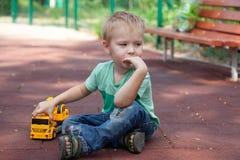 Chłopiec z niebieskimi oczami siedzi na pokrywie dziecka boisko z zabawką - żółty ekskawator Blondynka włosy, rozważny spojrzenie zdjęcia stock