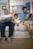 Chłopiec z ojca i dziadu obsiadaniem na kanapie zdjęcia royalty free