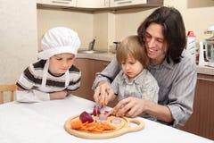 Chłopiec z ojciec rżniętą cebulą Zdjęcie Stock
