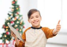 Chłopiec z pastylka komputerem osobistym pokazuje aprobaty przy bożymi narodzeniami Obrazy Stock