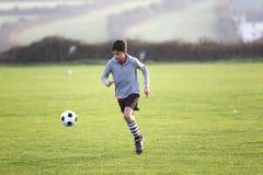 Chłopiec z piłki nożnej piłką outside Obrazy Stock