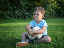 Chłopiec z piłki nożnej piłki obsiadaniem na trawie Obraz Stock