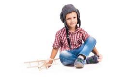 Chłopiec z pilotowym kapeluszu i zabawki samolotem fotografia stock
