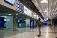 Chłopiec z plecak pozycją przy lotniskiem i patrzeć tablicę wyników Fotografia Royalty Free