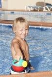 Chłopiec z podlewaniem może w pływackim basenie Obraz Royalty Free