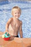 Chłopiec z podlewaniem może w pływackim basenie Obrazy Stock