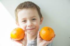 Chłopiec z pomarańczami w jego rękach obrazy royalty free