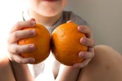 Chłopiec z pomarańczami w jego rękach zdjęcie royalty free