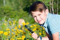 Chłopiec z powiększać - szkło w lecie obrazy stock