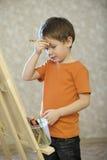 Chłopiec Z ręką Na czoło pozyci Przed sztalugą zdjęcia stock