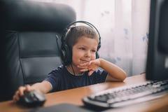 Chłopiec z słuchawki używać komputer Fotografia Royalty Free