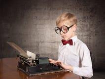 Chłopiec z starym maszyna do pisania Zdjęcia Stock