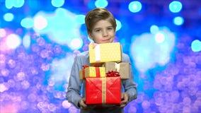 Chłopiec z stosem Bożenarodzeniowi prezentów pudełka zbiory