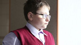 Chłopiec z szkłami przyglądającymi out okno zbiory