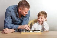Chłopiec z tata bawić się warcabów w domu zdjęcia stock