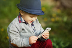 Chłopiec z telefonu obsiadaniem na trawie Zdjęcie Royalty Free