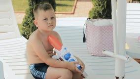 Chłopiec z wodnego pistoletu obsiadaniem na deckchair zbiory wideo