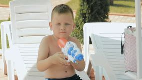 Chłopiec z wodnego pistoletu obsiadaniem na uśmiechu i deckchair zdjęcie wideo