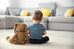 Chłopiec z zabawkarskim obsiadaniem na podłoga w żywym pokoju fotografia royalty free