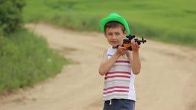 Chłopiec z zabawkarskim pistoletem wydaje czas na drodze zbiory
