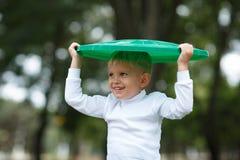 Chłopiec zabawę wśrodku recyling jałowego kosz outside Pojęcie ochrona środowiska pole kolorowego obraz royalty free