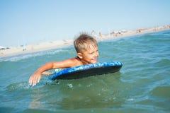 Chłopiec zabawę z surfboard Zdjęcia Royalty Free