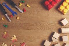 Chłopiec zabawek ramowy tło Kolorowi zabawek narzędzia, budowa bloki i sześciany na drewnianym stole, Odgórny widok Mieszkanie ni Obrazy Royalty Free