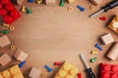 Chłopiec zabawek ramowy tło Zabawek narzędzia, budowa bloki i sześciany na drewnianym stole, Odgórny widok Mieszkanie nieatutowy Zdjęcie Stock