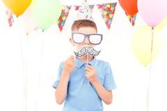 Chłopiec zakrywa jego twarz z urodzinowymi etykietkami obraz royalty free