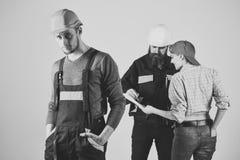 Chłopiec Zasilająca Zagadnienie twarzy chłopiec Brygada pracownicy, budowniczowie w hełmach, naprawiacze i dama dyskutuje kontrak fotografia royalty free